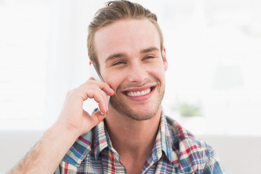 man smiling answering call